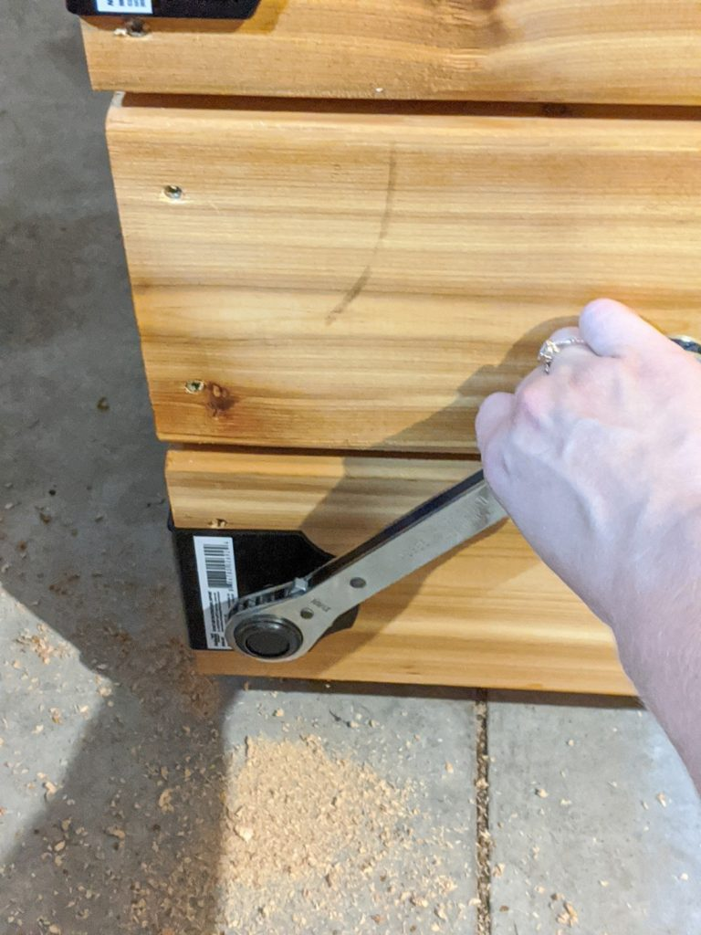 Installing the decorative hardware using a ratcheting wrench to put in the lag screws