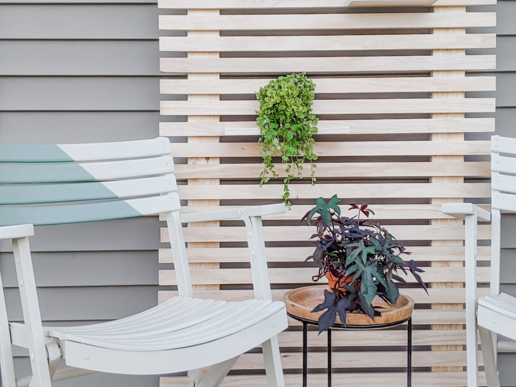 Close up of Painted Chairs and Wood Slat Plant Wall