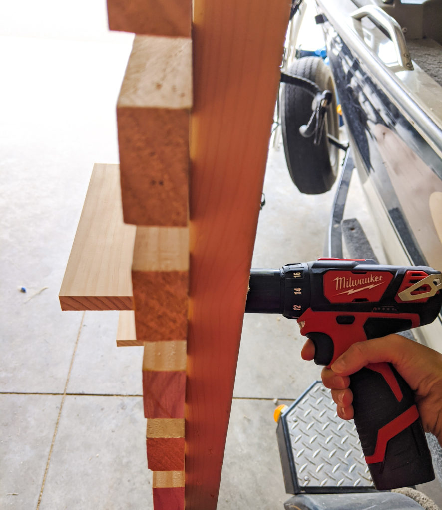 Attaching the shelves to the slat wall using screws and a drill