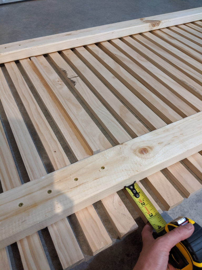 Measuring out the boards before screwing them into one another for the wood slat planter wall