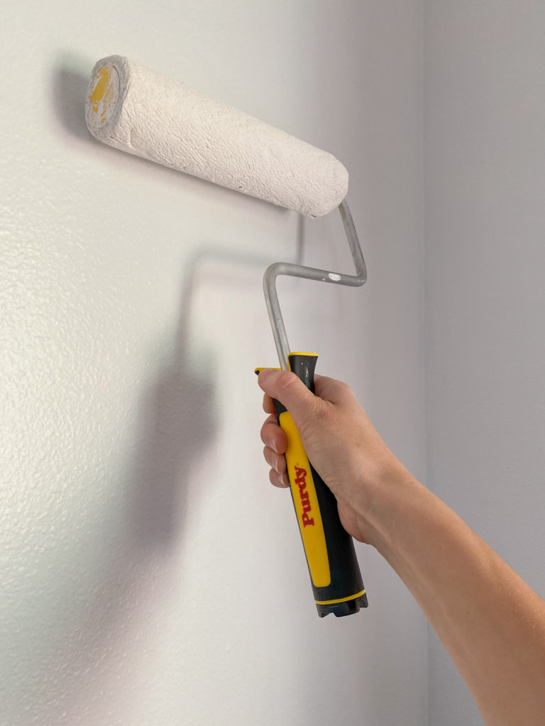 Purdy roller painting white paint on wall