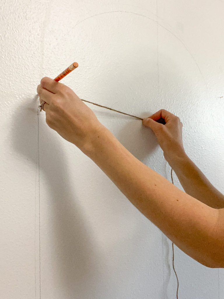 Drawing an arch on the wall using a string and a pencil