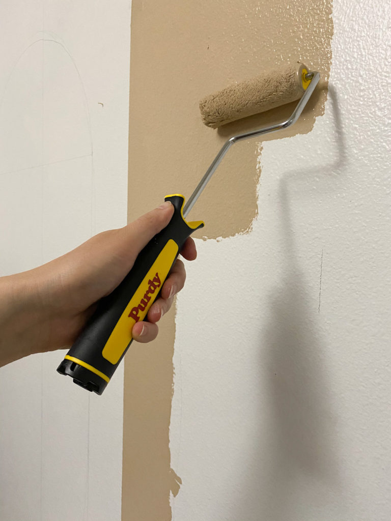 Using a Purdy mini roller to paint the design on the wall