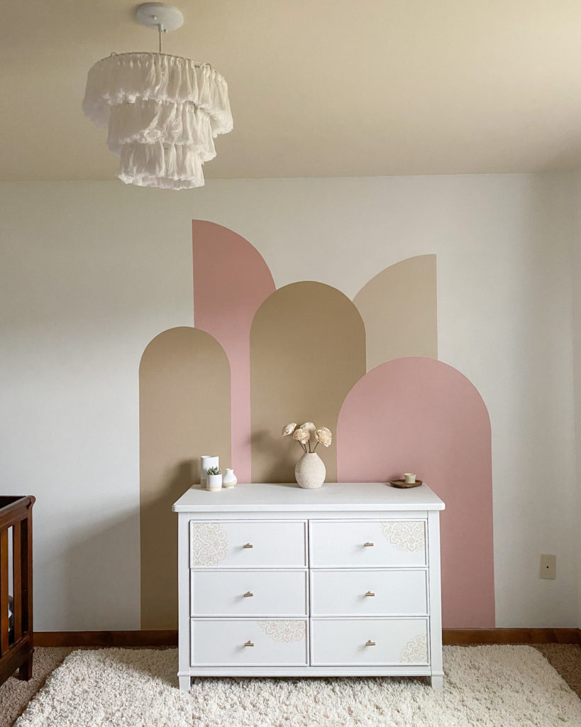 Modern boho little girl's room with tassel chandelier and modern arches color block wall
