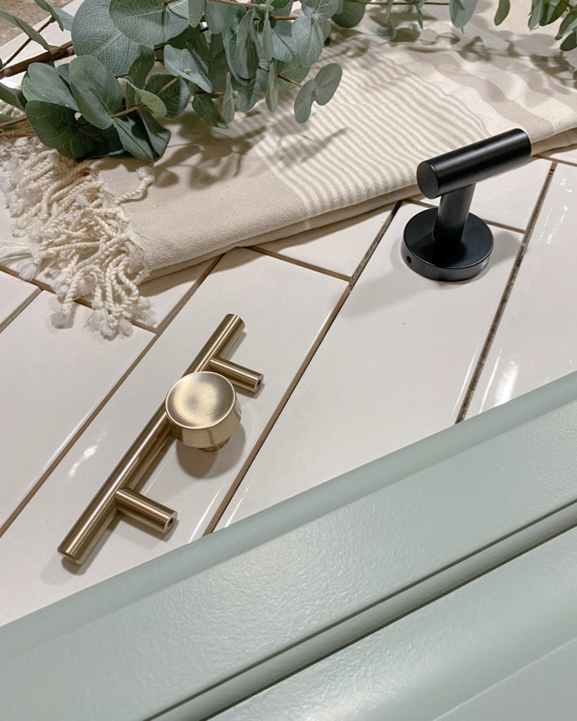 Bathroom mood board including white tile, brushed gold finishes and sage green cabinets