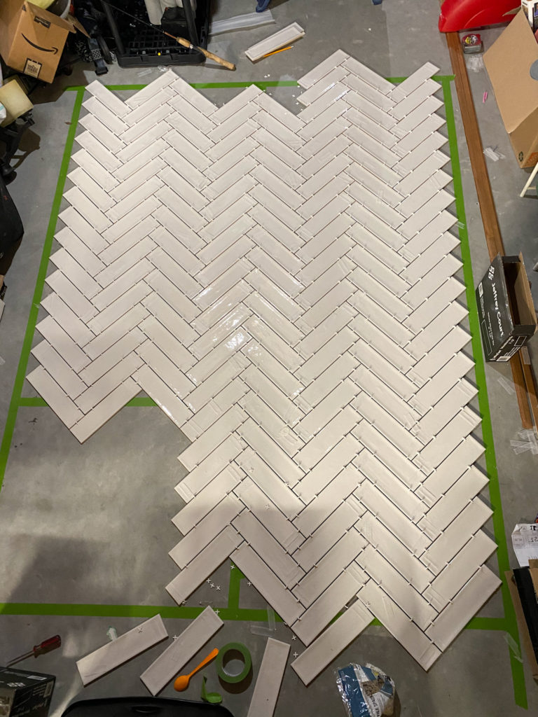 Laying out herringbone pattern on floor before tiling
