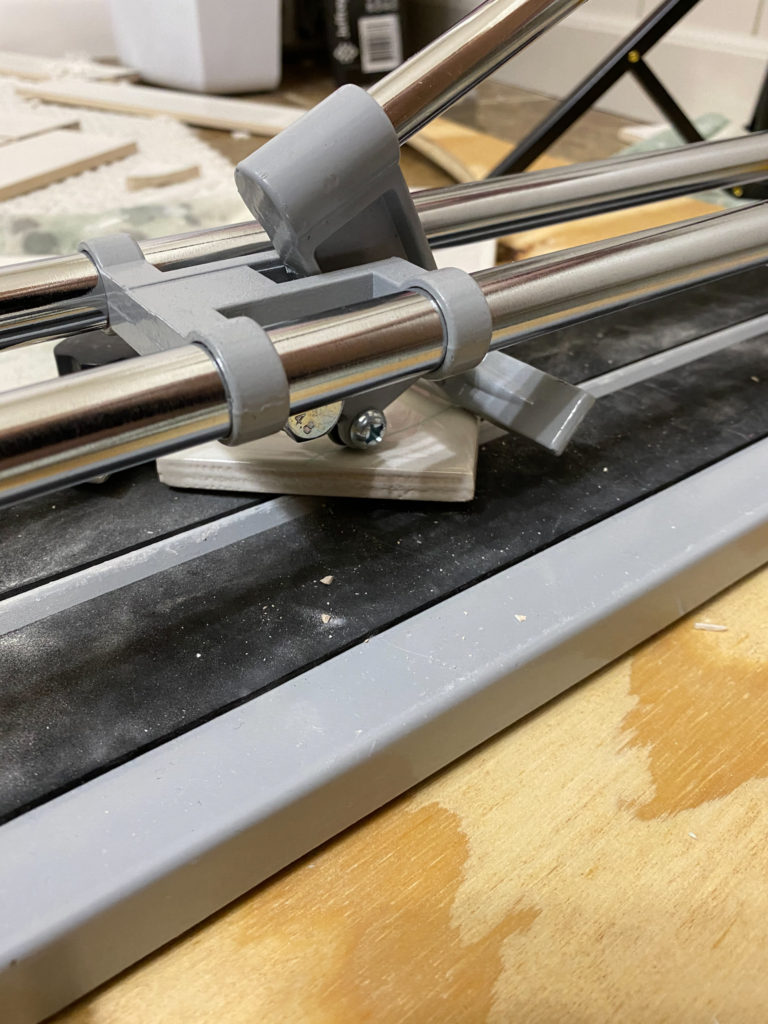 Scoring and snapping tiles with tile cutter for herringbone design