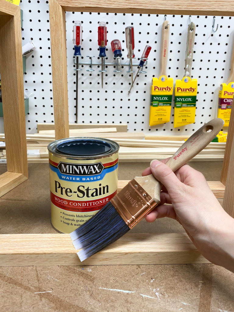Applying pre-stain wood conditioner to modern wall art frames