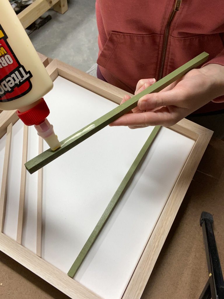 Gluing  wood dowels onto canvases for modern wall art
