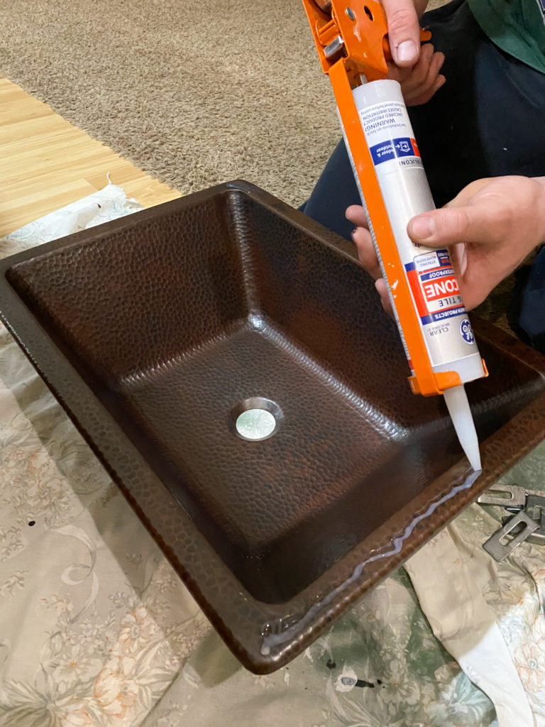 Applying silicone to sink to adhere to countertop