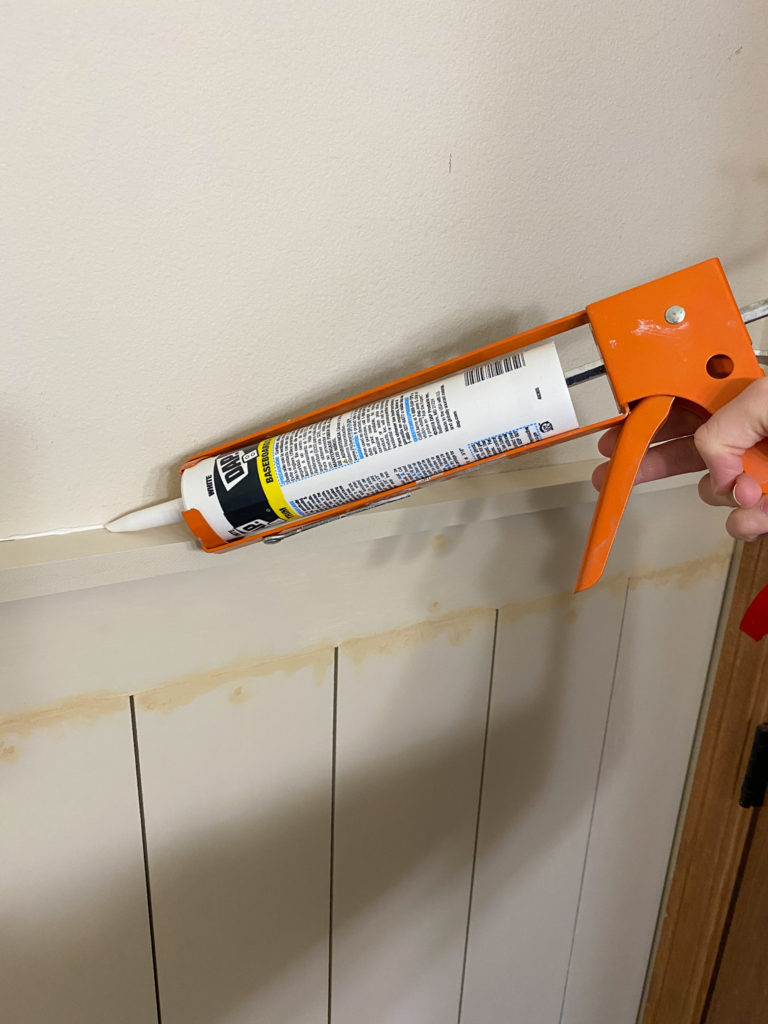 Caulking a line on top of faux shiplap wall