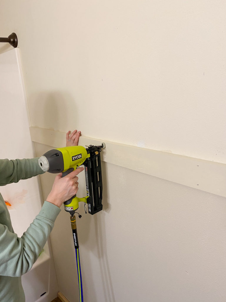 Using a nail gun to secure shiplap to the wall