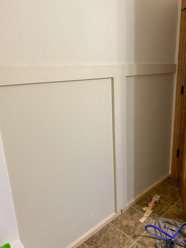 Attaching shiplap to a wall in the bathroom, starting with the middle piece