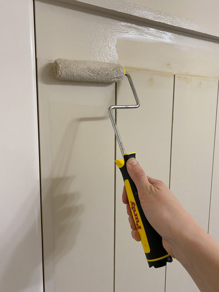 Applying paint to shiplap wall using Purdy mini roller