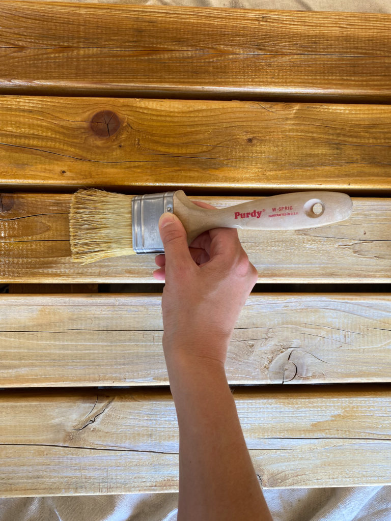 Applying Oil to Outdoor Furniture with a White Bristle Brush